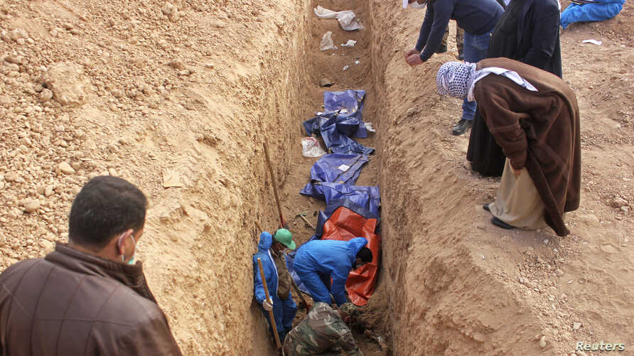 FILE - Men excavate remains of more than 25 men reportedly killed by Islamic State fighters on the outskirts of Saadia in Iraq's Diyala province, Jan. 15, 2015.