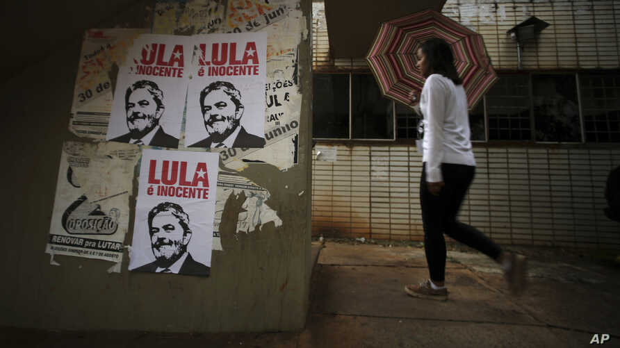 "This Jan. 29, 2018 photo shows a wall displaying posters with line drawings that depict Brazil's former President Luiz Inacio Lula da Silva and a message that says ""Lula is innocent"" in Portuguese, Brasilia, Brazil."