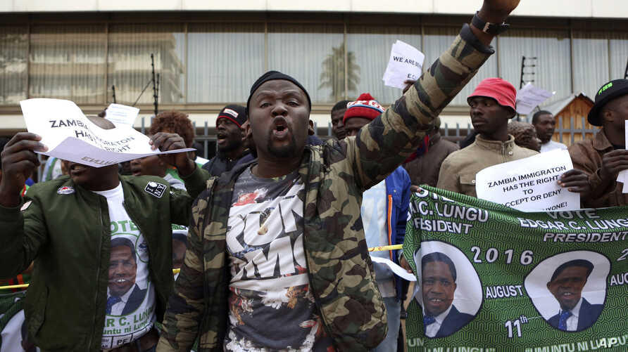FILE - Supporters of Zambian President Edgar Lungu react while supporters of Zambia's opposition leader, Hakainde Hichilema, picket alongside Democratic Alliance (DA) members outside the High Commission of Zambia, in Pretoria, South Africa, Friday Ma