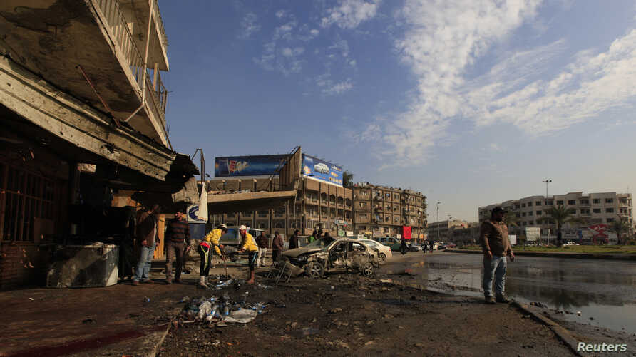Municipality workers clean the site of a bomb attack in Baghdad, Jan. 15, 2014.