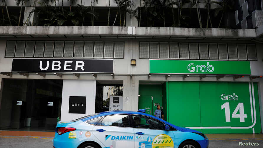 A ComfortDelgro taxi passes Uber and Grab offices in Singapore, March 26, 2018.