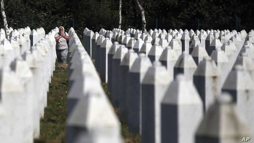 A Bosnian Muslim woman reacts as she walks among gravestones at the memorial centre of Potocari near Srebrenica, 150 kms north east of Sarajevo, Bosnia, Tuesday, Aug. 14, 2018.