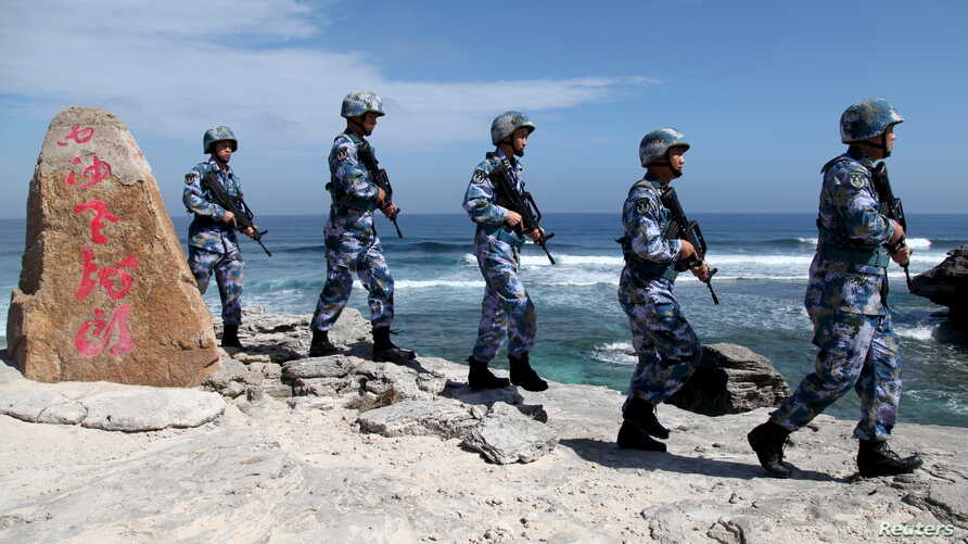 FILE - Soldiers of China's People's Liberation Army (PLA) Navy patrol at Woody Island, in the Paracel Archipelago, which is known in China as the Xisha Islands, Jan. 29, 2016.