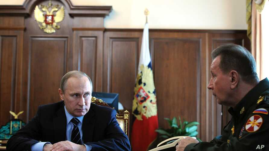 FILE - Russian President Vladimir Putin, left, and Commander-in-Chief of the Interior Ministry troops Viktor Zolotov attend a meeting in the Kremlin in Moscow, Russia, April 5, 2016.