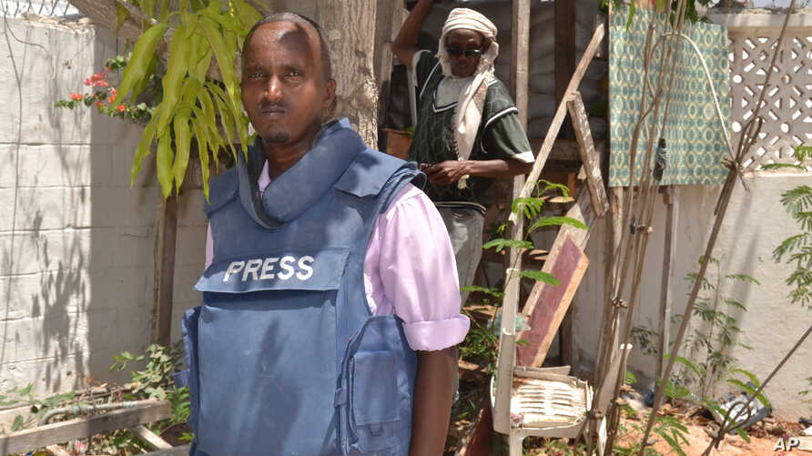 In this photo taken Saturday, March 22, 2014, Somali journalist Abdiaziz Mohamed Ali Haji, ,left, stands in radio Shabelle compound in Mogadishu, Somalia