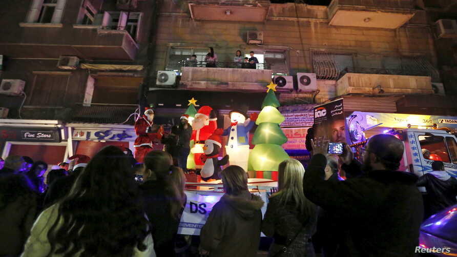 A man dressed as Santa Claus distributes gifts to children during a Christmas parade in Damascus, Syria, on Dec. 27, 2015.