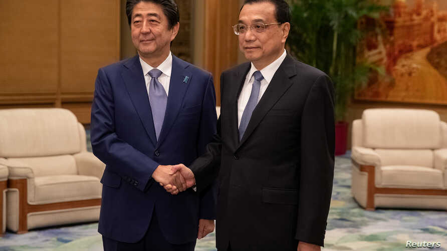 Chinese Premier Li Keqiang and Japanese Prime Minister Shinzo Abe shake hands during their meeting at the Great Hall of the People in Beijing, Oct. 25, 2018.