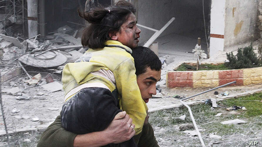 Syrian man carries his sister who was wounded in a government airstrike hit the neighborhood of Ansari, in Aleppo, Syria, Sunday, Feb. 3, 2013.