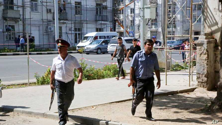 Police officers secure an area in the capital of Tajikistan, Dushanbe, where several Interior Ministry special forces officers were shot dead earlier on Friday,  Sept. 4, 2015, in attacks reportedly mounted by groups led by disaffected deputy defense