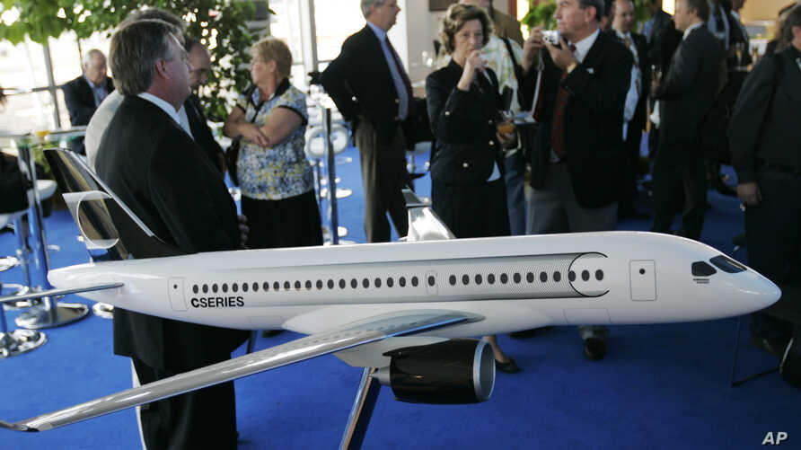 "FILE - People gather around a model of C Series Bombardier airplane on the eve of the Farnborough aerospace show,  Farnborough, England, July 13, 2008. Boeing has accused Bombardier of receiving government subsidies that let it engage in ""predatory p"