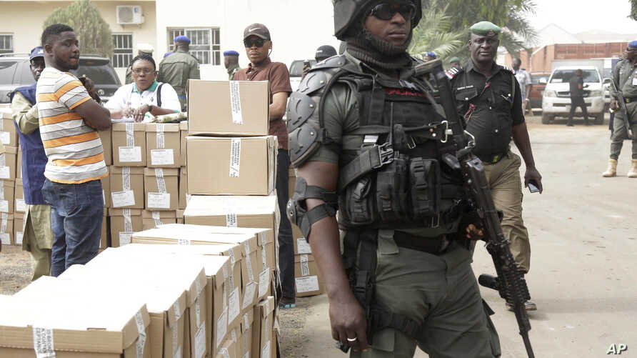 A police officer stands guard as electoral workers load ballot papers into trucks to be transported to polling stations, at the Independent National Electoral Commission in Yola, Nigeria, Feb. 15, 2019.