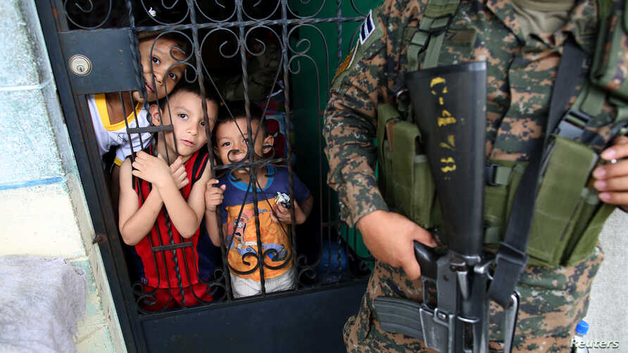 Children watch police officers as they paint over graffiti related to the MS-13 gang in the La Vega neighborhood in San Salvador, El Salvador, Sept. 26, 2017.