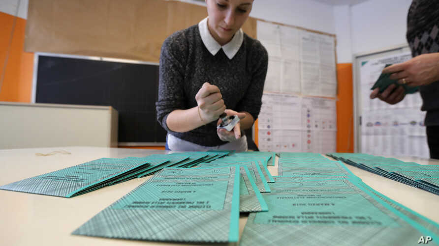 Polling station workers prepare ballots in Rozzano, near Milan, Italy, March 3, 2018. An election in Italy on Sunday will determine the makeup of the nation's Parliament and its next government.