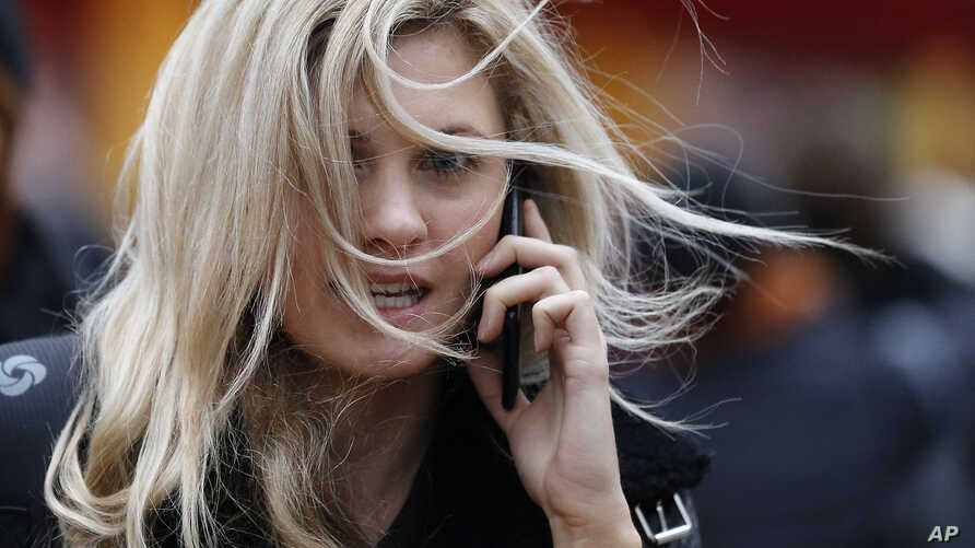 FILE - The hair of a woman is blown by the wind on a blustery day in London, Dec. 30, 2015. Heavy rains and gusty winds are causing more problems for residents in large swaths of Britain.
