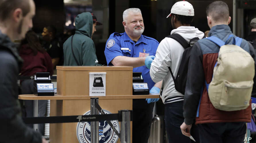 A TSA worker checks hands an identification card back to a traveler at Seattle-Tacoma International Airport in Seattle, Jan. 25, 2019. Yielding to mounting pressure and growing disruption, President Donald Trump and congressional leaders on Friday re