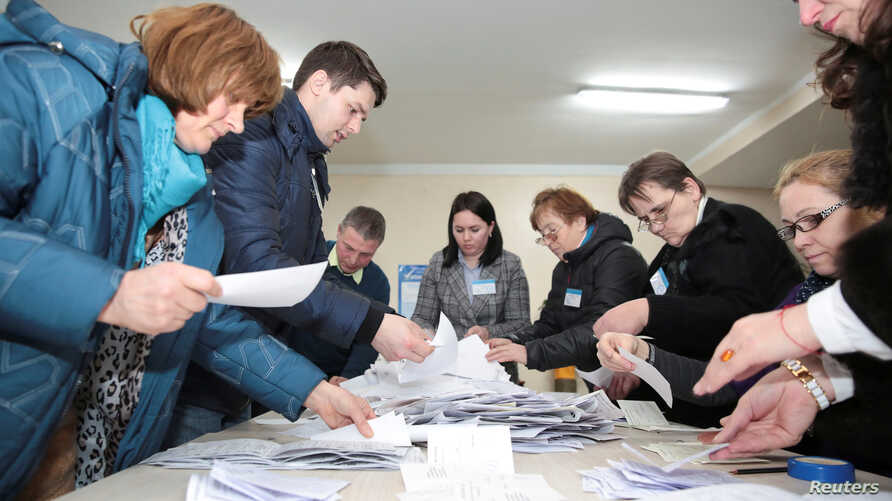 Members of a local electoral commission count votes following a parliamentary election in Chisinau, Moldova, Feb. 24, 2019.