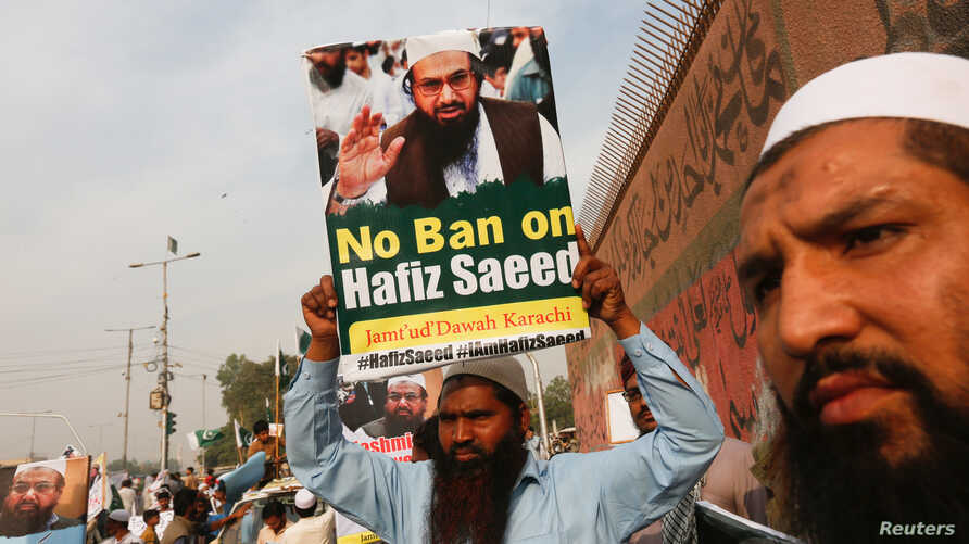FILE - A supporter of Islamic charity organization Jamaat-ud-Dawa (JuD), carries a sign with others as they listen the speech of leaders (unseen) to condemn the house arrest of Hafiz Muhammad Saeed, chief of (JuD), during a protest demonstration in K