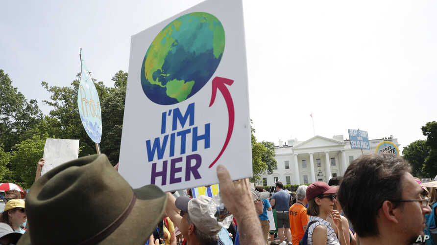 Participants walk along Pennsylvania Ave., in front of the White House in Washington, during a demonstration and march, April 29, 2017. Thousands of people gather across the country to march in protest of President Donald Trump's environmental polici