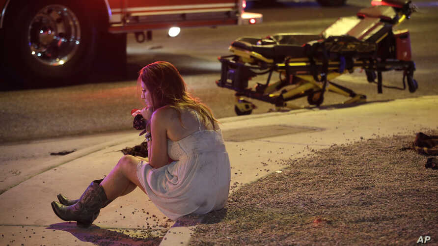 FILE - In this Oct. 2, 2017, file photo, a woman sits on a curb at the scene of a shooting outside of a music festival along the Las Vegas Strip. Months after Facebook and Google announced major efforts to curb the spread of false stories masqueradin