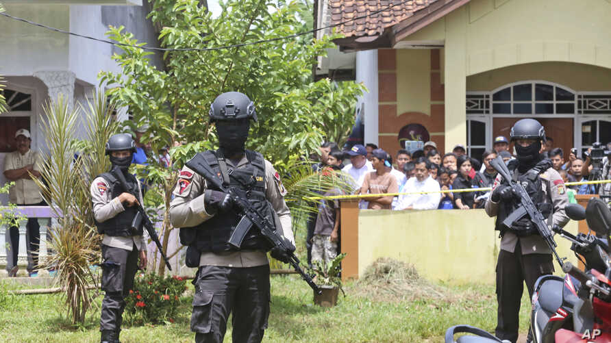 Police officers stand guard at a residential neighborhood where police conducted a raid on a house used by suspected militants, in Tangerang, Indonesia, Dec. 21, 2016.