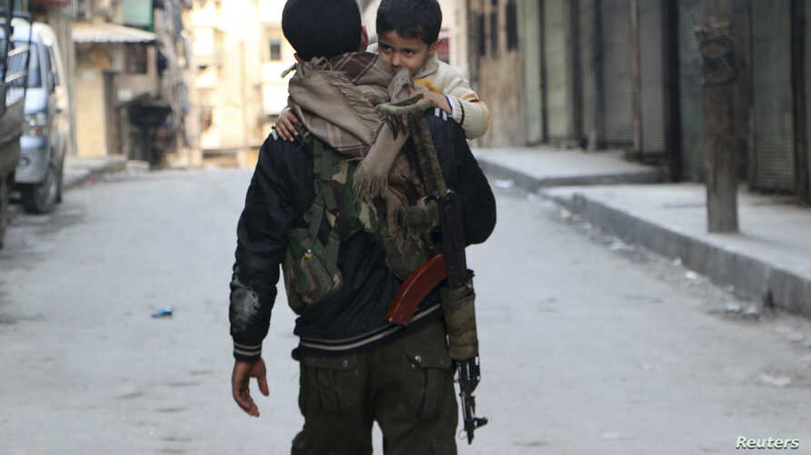 A Kurdish fighter from the Popular Protection Units (YPG) carries his son as he walks along a street in Aleppo's Sheikh Maqsoud neighbourhood February 18, 2014. REUTERS/Hosam Katan (SYRIA - Tags: POLITICS CIVIL UNREST CONFLICT) - RTX1928A