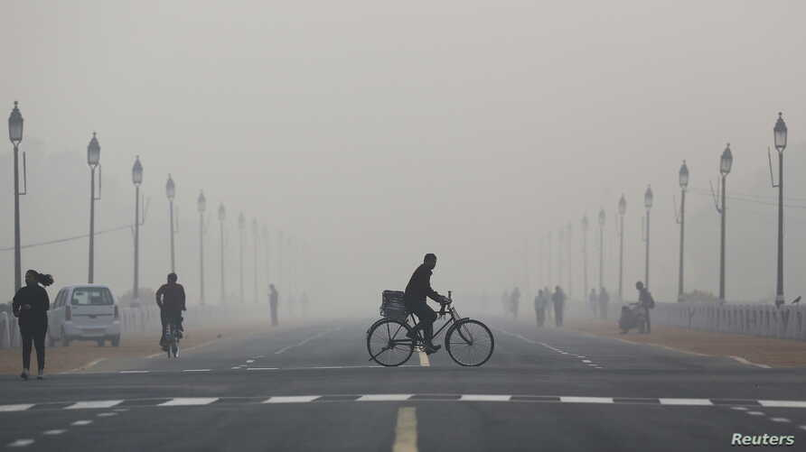 A newspaper vendor rides his bicycle on a smoggy morning in New Delhi, India, December 1, 2015.