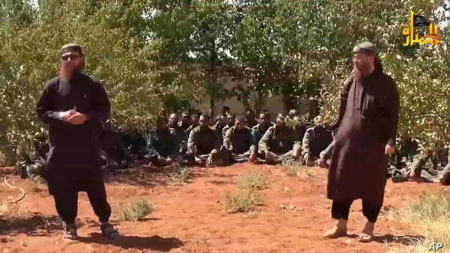 This image made from video posted on a militant social media account shows U.N. peacekeepers from Fiji, background, held captive by militants from the Nusra Front in Syria, Sept. 11, 2014.