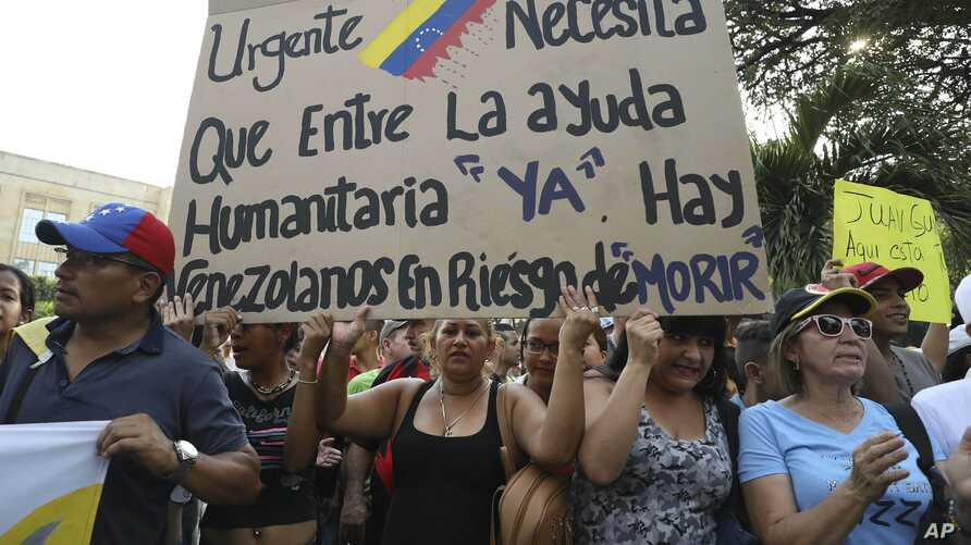 "Venezuelans living in Colombia protest the government of Venezuela's President Nicolas Maduro and its blocking of humanitarian aid in Cucuta, Colombia, Feb. 12, 2019. The sign reads, ""Urgent. The entry of humanitarian help is needed now. There are Ve"