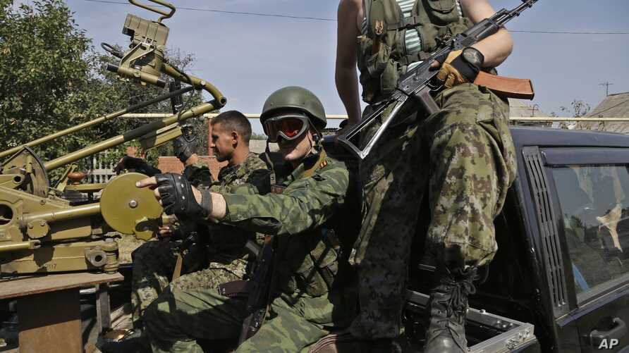 Pro-Russian rebels sit in their car with a heavy machine gun in Donetsk, eastern Ukraine, Sept. 7, 2014.
