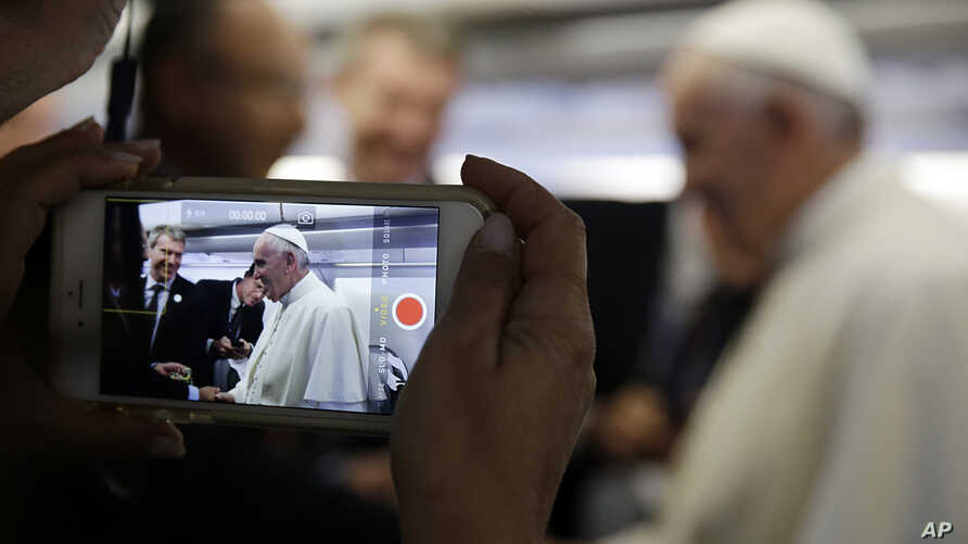 FILE - A journalists uses his mobile phone to take a picture of Pope Francis aboard the papal airplane.