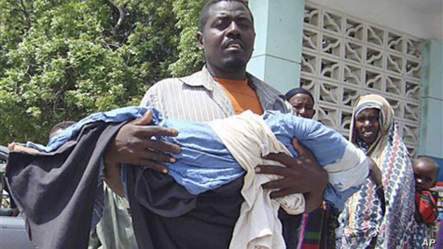 A man from southern Somalia carries the body of his dead child from Banadir hospital in Mogadishu, Somalia, Monday, July 25, 2011