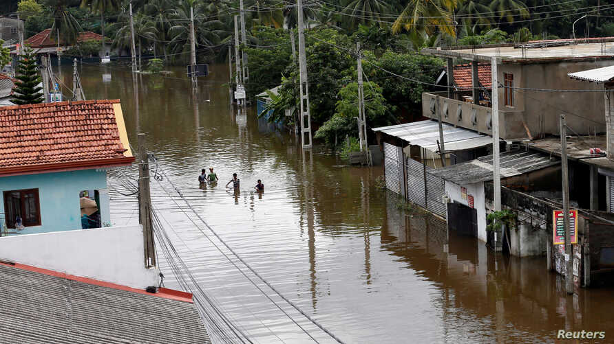 A group of men walk through a flooded road during a rescue mission in Nagoda village in Kalutara, Sri Lanka, May 29, 2017.