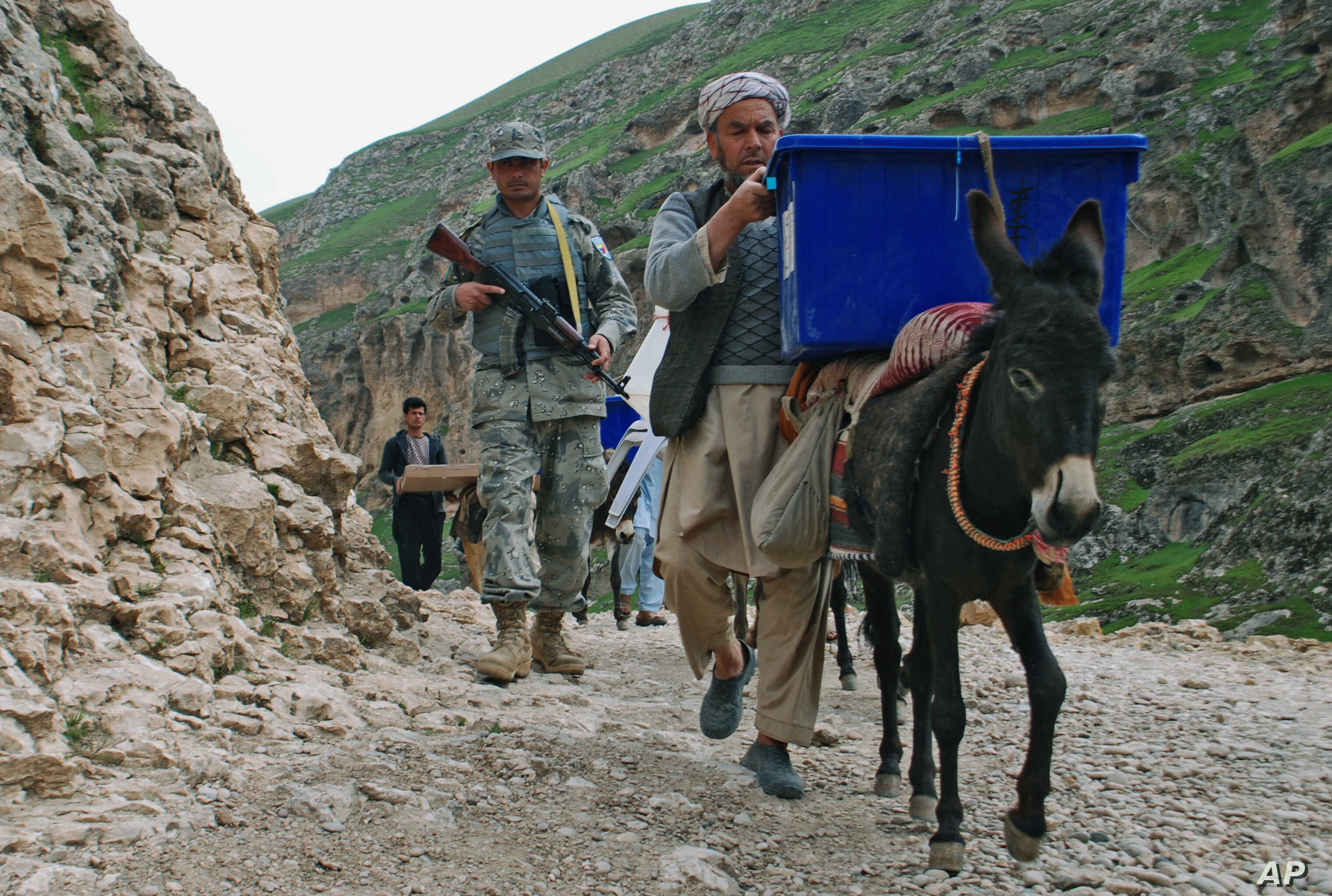 Afghan election workers use donkeys to transport ballot boxes and election materials to polling stations as walking through Mazar-i-Sharif to Kishindih district in Balkh province, Afghanistan, April 3, 2014.