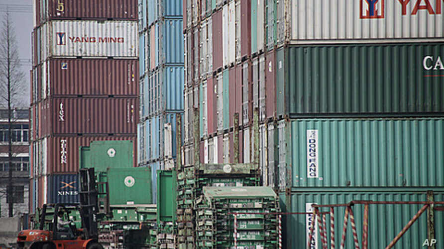 Forklift arranges shipping containers near Shanghai port, China, March 2, 2011 (file photo).