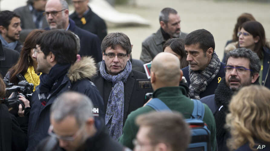 Ousted Catalan leader Carles Puigdemont (C) walks in the park with elected Catalan lawmakers of his Together for Catalonia party in Brussels on Jan. 12, 2018.