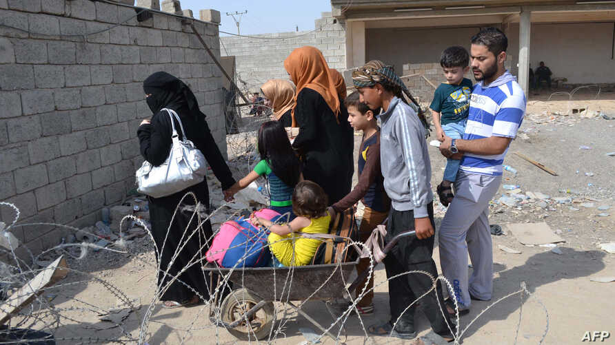 Iraqi families fleeing Islamic State (IS) group advance in their towns arrive to take refuge in a Kurdish-controlled area in Mullah Abdullah, some 25 kms west of Kirkuk, Oct. 15, 2014.