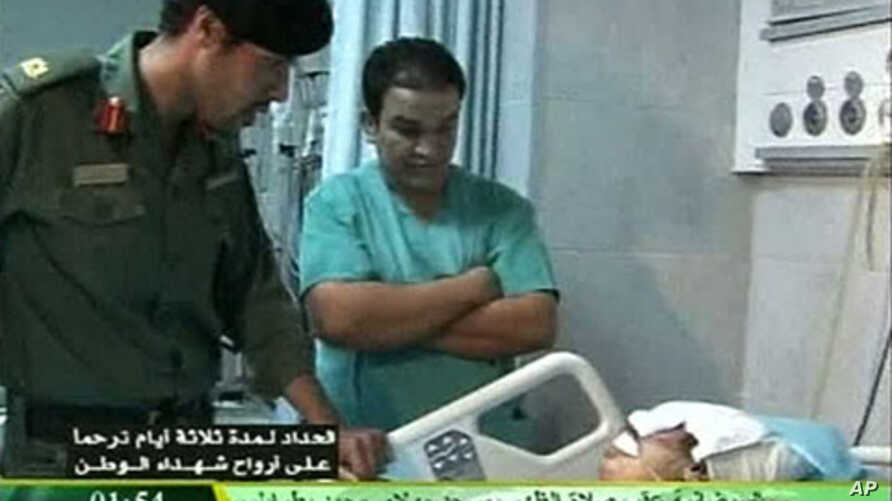 Still image from video footage by Libyan state television on August 9, 2011, shows what it says is Khamis Gadhafi (L) visiting wounded Libyans in a hospital