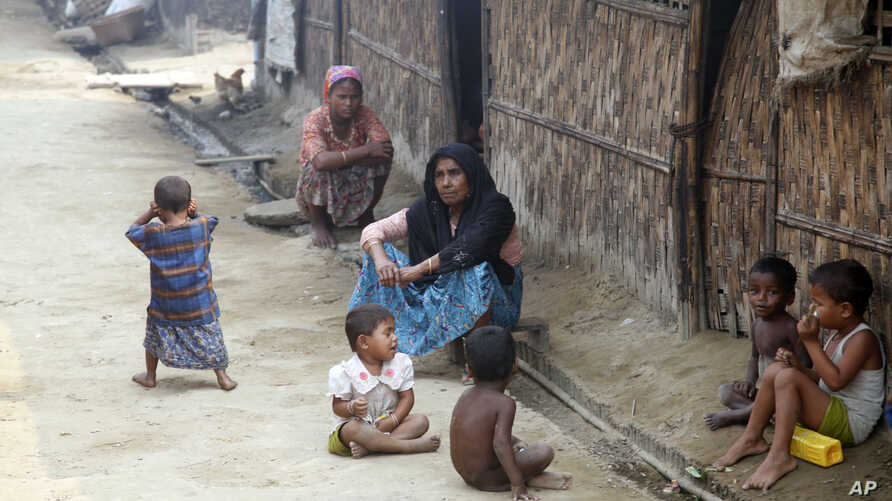 "Myanmar Muslims, who identify themselves as long-persecuted ""Rohingya"" Muslims, sit on the ground at Da Paing camp for Muslim refugees in north of Sittwe, Rakhine State, western Myanmar, April 2, 2014."