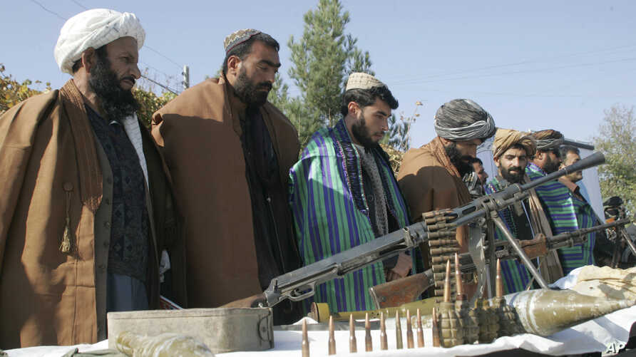 FILE - Taliban fighters line up as they hand over their weapons to join the peace process in Herat, Afghanistan, Nov. 3, 2012.
