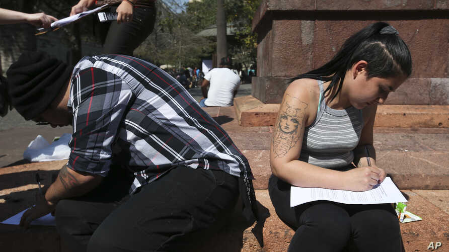 Catholics fill out forms seeking the formal renunciation of their religion in protest of the innumerous cases of sexual abuse by the clergy, in Santiago, Chile, Sept. 8, 2018.