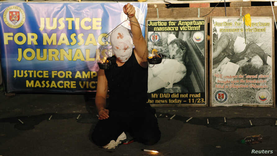 "A masked Filipino artist holds up a replica of a burning weighing scale signifying justice to commemorate the 2nd year anniversary of the ""Maguindanao Massacre"" at the National Press Club compound in Manila November 23, 2011."