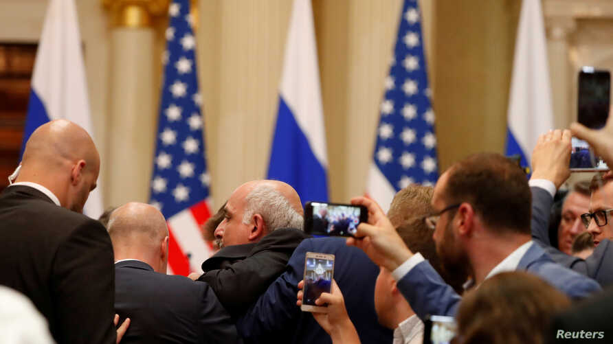 Security personnel remove a reporter, Sam Husseini, ahead of a joint press conference by U.S. President Donald Trump and Russian President Vladimir Putin in Helsinki, Finland, July 16, 2018.