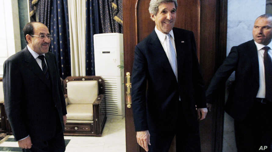 U.S. Secretary of State John Kerry, second right, leaves after meeting with Iraq's Prime Minister Nouri al-Maliki, left, in Baghdad, Iraq, March 24, 2013.