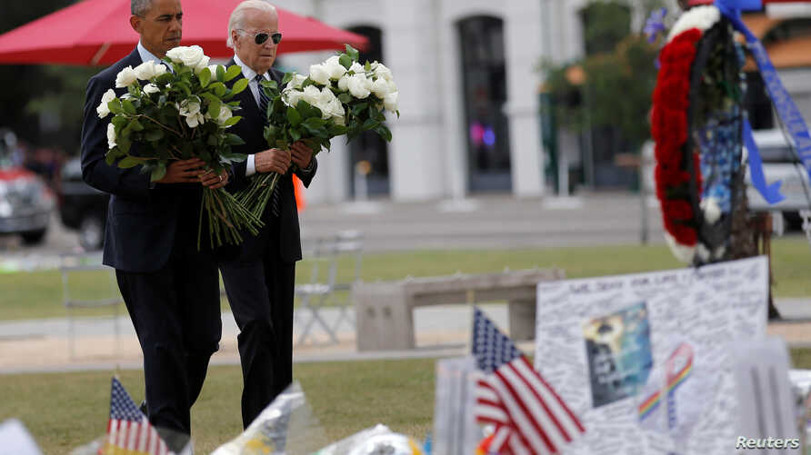 President Barack Obama, left, and Vice President Joe Biden place flowers at a makeshift memorial for shooting victims of the massacre at a gay nightclub in Orlando, Fla., June 16, 2016.