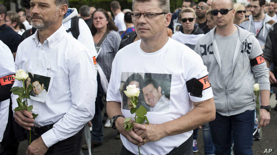 Police officers walk to pay homage to the two slain colleagues during a white march in Mantes-la-Jolie, west of Paris, June 16, 2016.