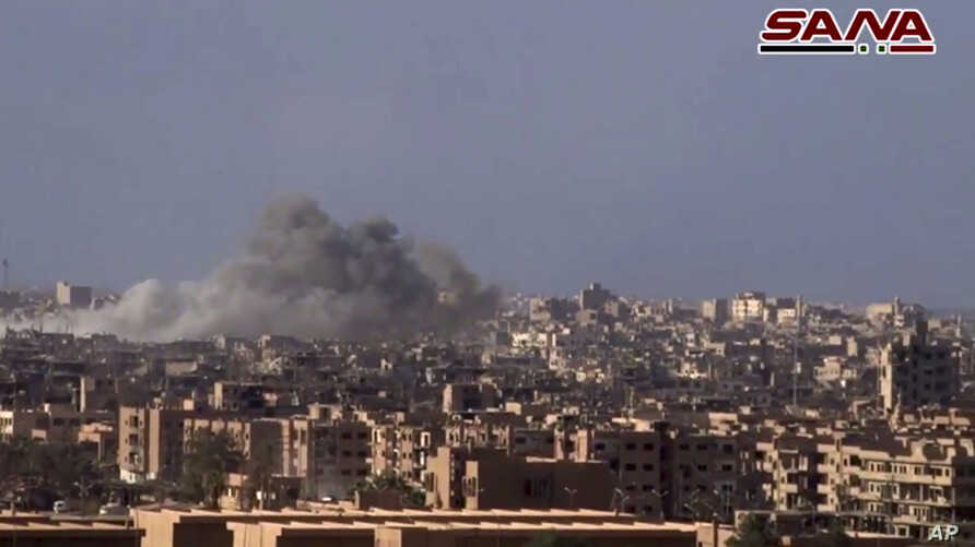 This frame grab from a video released Nov. 2, 2017, by the Syrian official news agency SANA shows smoke and debris rising after Syrian government shelling of the Deir el-Zour city during a battle against Islamic State militants, Syria. The Syrian arm