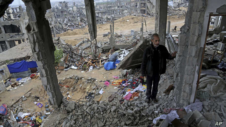 FILE - A man stands in rubble of his house, destroyed in this year's Israel-Hamas conflict, in the Shijaiyah neighborhood of Gaza City, Nov. 24, 2014.