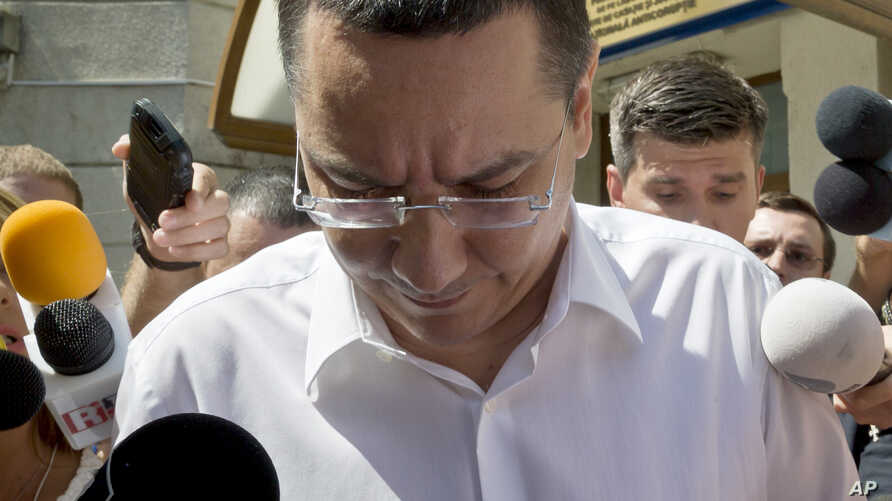 FILE -  Romanian Premier Victor Ponta is surrounded by media as he exits the national anti-corruption prosecutors office.