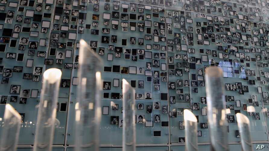 FILE - Pictures of missing people are displayed at the Memory and Human Rights Museum during its inauguration in Santiago, Chile.
