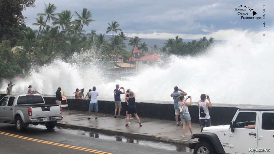 Incoming waves tower over bystanders in Kona, Hawaii, U.S., Aug. 23, 2018 in this still image from video obtained from social media. (Ryan Leinback)